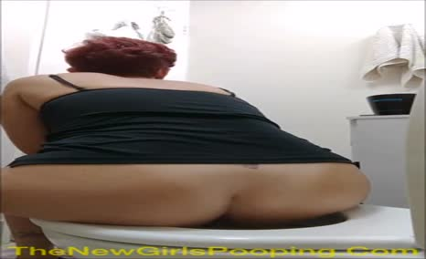 A mature red haired lady takes a shit with a good view with it coming it out