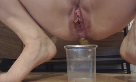 Shaved babe filled a cup with poop